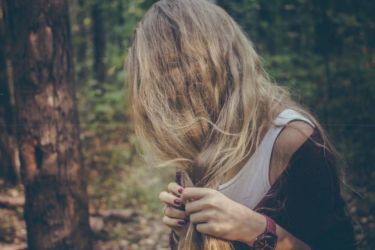 Frau im Wald flechtet ihr Haar
