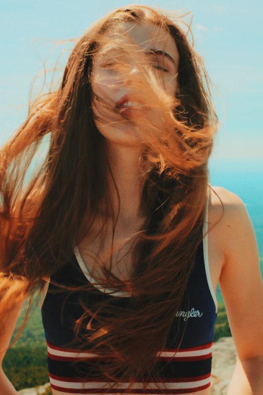 Frau mit langen roten Haaren im Wind