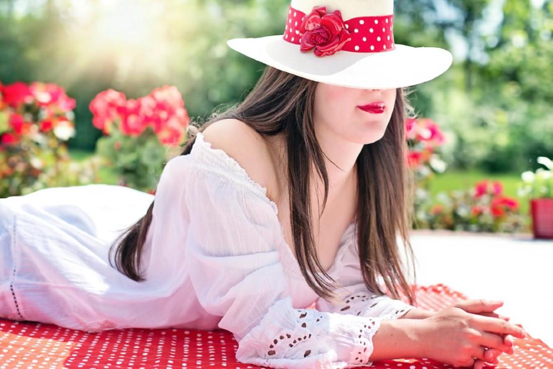 Frau mit Hut und langem Haar auf Decke